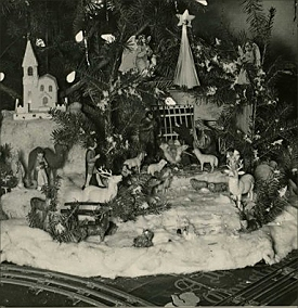 This is a detail from a photo on collector Ted Althof's site. Track for a Standard Gauge train is in the foreground, the Nativity is in the center right position and a Japanese pasteboard cathedral is at the left. You can also see C6 lightbulbs and 'icicles' made of lead foil. The photo probably dates between 1920 and 1939. Click to see the whole photo.
